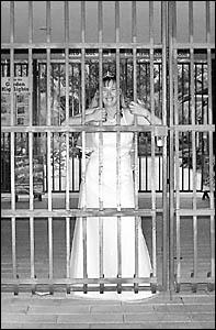 One to tell the children . . . bride Kellie stands behind bars at the North Coast Regional Botanic Garden.