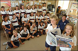 WINNERS: St James Primary School Year 5 students Jack Berger, left, and Tess Ellem read The Daily Examiner while their classmat