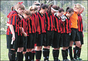 Coffs United Lionesses players bow their heads in memory of club coach, Michael King, who died last Friday.
