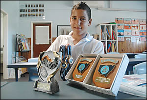Young swimming star Djaran Smith with his collection of medals and trophies won in the pool.