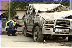 Calliope Police Senior Constable Paul Foley examines a vehicle involved in a fatal accident