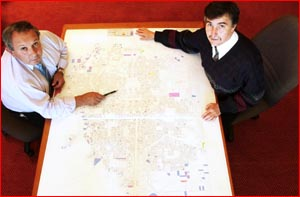 Kevin Wruck and Joe Ramia scan maps homing in on the city?s big domestic water users. Picture: KEVIN FARMER