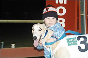Braiden Merillo gives his grandfather?s greyhound Look Fellas a congratulatory hug.