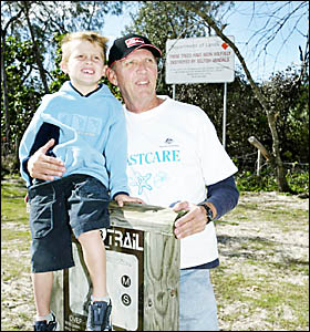KINGSCLIFF Dune Care?s Peter Langley with his grandson Jack Nosworthy in front of a sign aimed at shaming tree vandals. D95878B