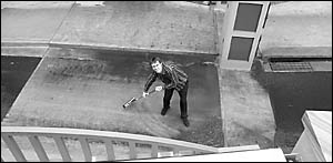 Planet Music manager Jamie Houston sweeps away rainwater from in front of the levee gates next to his store.