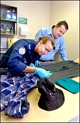 Gladstone Police Scenes of Crime Snr Const Carmen Loneragan and CIB Det Snr Const Dave Connolly and clothes from the robbery.
