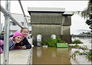 LEVEL CHECK: Meleah and Ellese Morrissey are pictured watching the flood levels at the levee wall near the pump station in Lism
