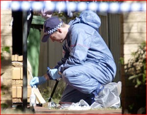 A scientific officer checks a unit in w ich three males were killed. Pictures: NEV MADSEN