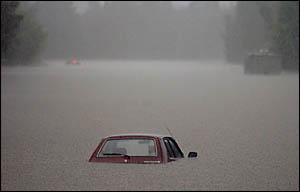 A submerged vehicle on a flooded main road at Robina. An estimated 600mm of rain was dumped on the Gold Coast. This was the equ