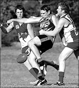 Robbie Zeegers (centre), who was one of the Saints? stars with five goals, gets his kick away despite the attention of North Co