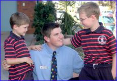 Riley ,5, (left) and Lucas Montgomery, 7, give deputy principal Nic Constable an appreciative hug.  kids220705-1