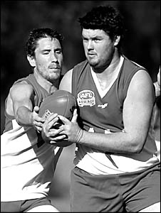 Todd Gill from North Coffs tries to keep possession despite the attentions of Coffs Swans player Ben Wyld in the match at Advoc