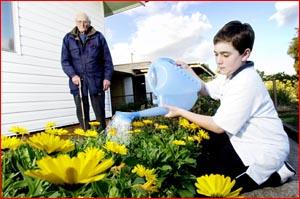 Alex Bloom, 12, helps Percy Urquhart, 87. Picture: NEVILLE MADSEN