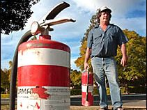 Peter Barnier with the two fire extinguishers he used to douse the flames of the burning car.
