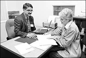 Peter Basra helps Annette Mackinnon with her tax return. Photo: SUE DOUGLASS 05080607B