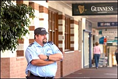 Security guard Greg Peet watches over the entrance of the Grand Hotel after its doors were closed yesterday.