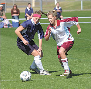 Chloe Gal, right, goes on the attack for John Paul College.