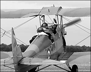 Looking the part in their uniforms, pilots Chris Tulk and Brett Clowes fly off with John Norton?s Tiger Moth, headed for its ne