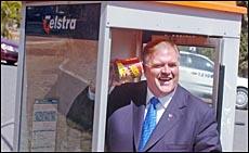 Federal Opposition leader Kim Beazley stands in Glen Eden's empty phone box.