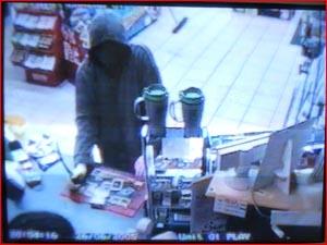 Security camera image of a knife-wielding Daniel Stephen Cay demanding money.