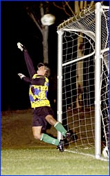 Clinton goalkeeper Roger Bailey in action making a fine save.