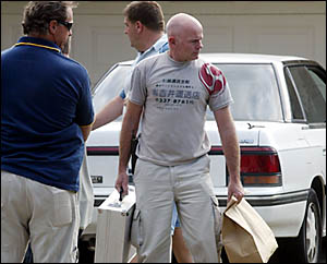 TWEED detectives carry away goods as evidence from a drug bust carried out at West Tweed Heads yesterday afternoon.