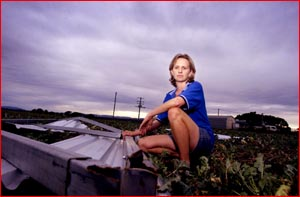 Donna Heit, of Lockyer Sheds, with a part of her shed that was blown across a neighbouring paddock. Picture: Kevin Farmer