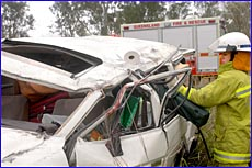Jeremy Lanzon from Calliope Fire Brigade clears up the scene after a single vehicle accident on the Bruce Highway yesterday.