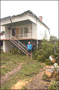 TIMBER!: Keith Morris stands outside his Oliver Street home after the clean-up from Thursday?s storm.