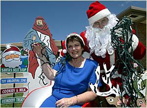 FESTIVE CHEER. Elanora?s Boab Street ?Santa? - alias resident Len Hull - and Cr Daphne McDonald get into the festive mood durin