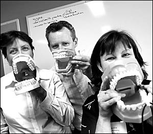 Dental therapist Jennifer Stokes, Dr Peter King and dental hygienist Linda Wallace with their sets of pearly whites at the Smil