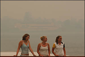 HAZY DAYS: Rebecca Zaffino, 17, Amanda Jarasius, 17, and Ashleigh Peppernell, 15, look for the river as it disappears amongst t