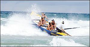 The South Curl Curl women?s crew crash through the wind-blown Park Beach surf.