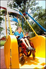 Darcy Keefe, with the help of mum Margie, was the first child to ride the new swing.