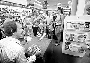 The host of the ABC?s Australia All Over radio program, Ian ?Macca? McNamara, signs books for fans at the Park Beach Plaza?s Dy