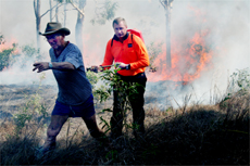 George Budge (left) and Jim Shack rush to contain the bushfire at Woodbury yesterday.
