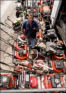 Maclean Motors mechanic Josh Welch with just a few of the mower repairs that have come in during the wet.