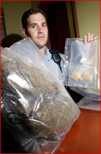 Constable Damian Carroll holds up nearly one kilogram of cannabis and amphetamine seized by police. Image: Neville Madsen