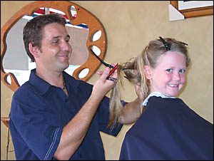 Brearna Solomons-Hickson, 5, getting ready for the new school year with hairdresser Mark Farnsworth yesterday.