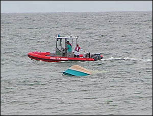 Members of the Wooli Volunteer Rescue Association tow the boat toward land.