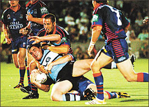 Sharks? prop Hutch Maiava cops a ?welcome to Coffs Harbour? tackle from the Knights? defence.