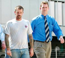 Rockhampton bikie Michael Miller (left) is taken into custody in 2003 by former Rockhampton police officer Luke Peachey.
