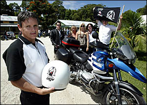 JEFF Kleem with the helmet and bike of his best mate, Alan ?The Prez? Bartrim, with family and friends of Alan at his funeral y