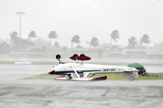 HOLD ON: A plane rests upside down on the runway at Cairns.