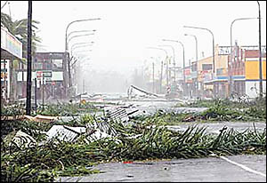 The main street of Innisfail yesterday ? a wasteland of branches and roofing iron torn from sheds and buildings. The Australian