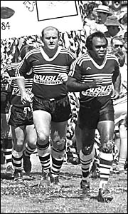 Gary Jovanovich follows Lower Clarence captain-coach Don Waters on to Frank McGuren field, at the start of the 1984 Group One r
