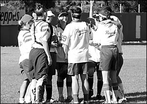 Members of the Royals Softball Club A reserve team gather in a huddle to celebrate their grand final win over Woolgoolga where