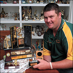 Cricket star Todd Gill holds his Bill Rae medal amongst his many other cricket trophies.