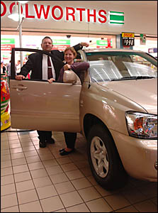Woolworths manager Wayne Avery, left, congratulates local woman Natalie Hollier, after she won a Toyota Kluger.