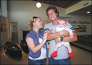 Welcome home . . . Shaun Cansdell is greeted by partner Heidi and daughter Paris at the Coffs Harbour airport yesterday afterno